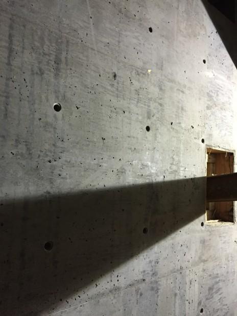 Béton noir, tirants et poutre en acier. Black concrete, steel ties and a steel beam.